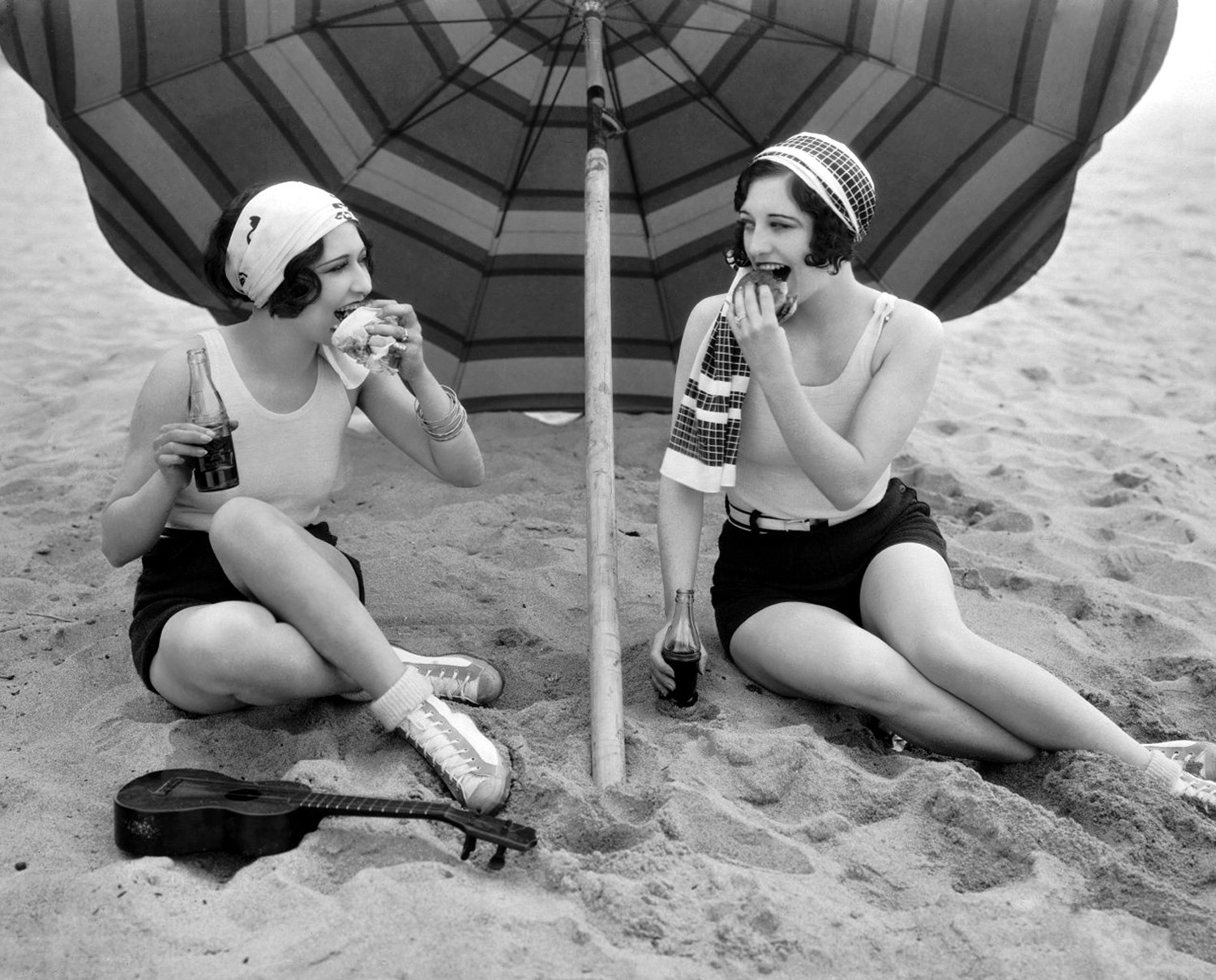 24th March 1927: American actress Joan Crawford (1904 - 1977) enjoys a picnic on the beach with fellow actress Dorothy Sebastian, left (1906 - 1957).