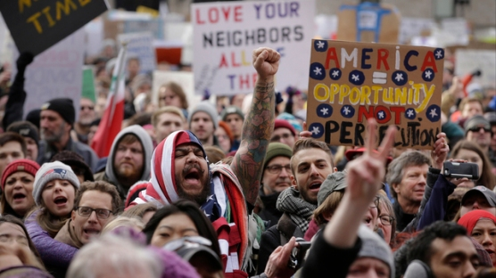 Izzy Berdan, of Boston, center, wears an American flags as he raises his arm and chants slogans with other demonstrators during a rally against President Trump's order that restricts travel to the U.S., Sunday, Jan. 29, 2017, in Boston. Trump signed an executive order Friday that bans legal U.S. residents and visa-holders from seven Muslim-majority nations from entering the U.S. for 90 days and puts an indefinite hold on a program resettling Syrian refugees. (AP Photo/Steven Senne)